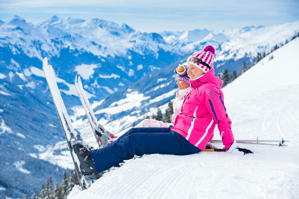 Two women sitting on the snow in Zillertal, Austria