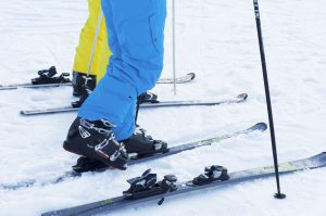 Feet put in narrow ski boots and skis
