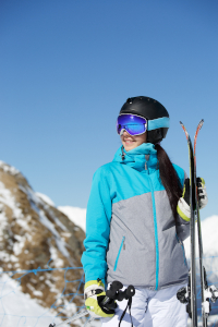 Photo of young smiling female athlete looking away in helmet with skis in hand against blue sky and snowy hill during day