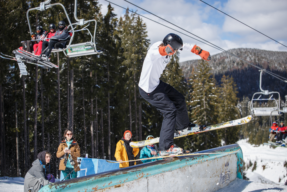 Ski rider grinds on rail with twintips in sunny winter day
